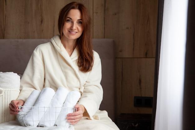 Junge frau im warmen bademantel steht nahe fenster und hält korb mit aufgerollten weißen handtüchern. frische aus gewaschenem leinen. natürliches textil. spick-and-span-konzept. gut bestellt.