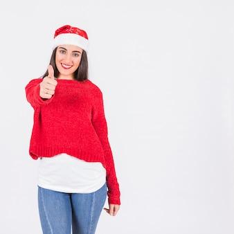 Junge frau im weihnachtshut mit dem daumen oben