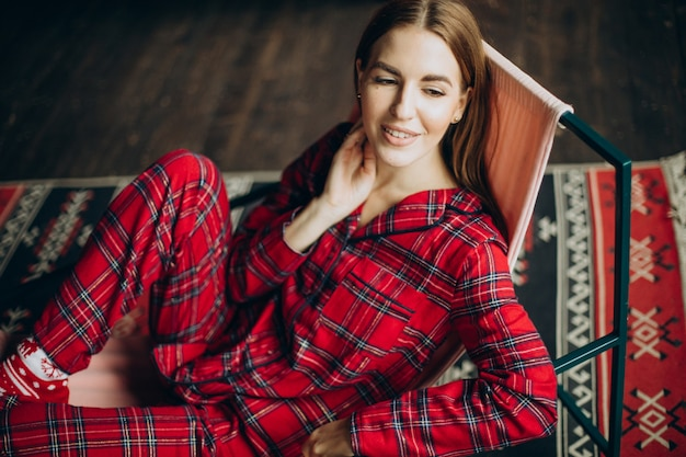 Junge frau im weihnachtspyjama, der auf stuhl sitzt