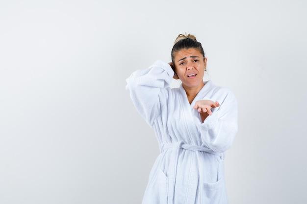 Junge frau im weißen bademantel, die die hand ausstreckt, als sie etwas erhält, während sie die hand hinter dem kopf hält und verärgert aussieht
