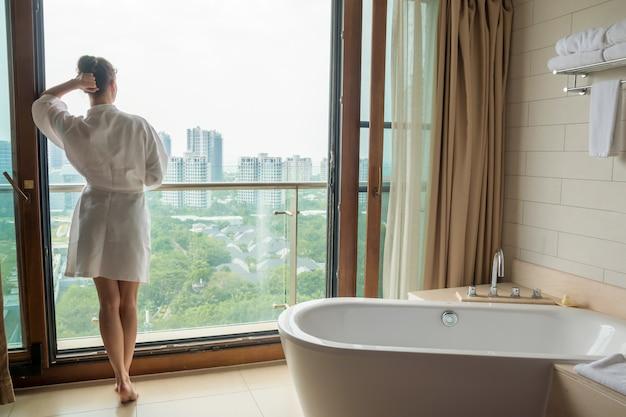 Junge frau im weißen bademantel im luxusbad mit blick auf die stadt