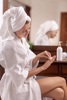 Junge frau im weißen bademantel mit einem handtuch auf dem kopf