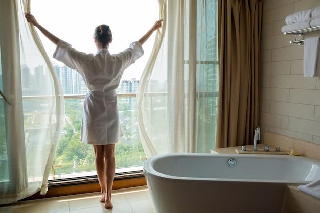 Junge frau im weißen bademantelöffnungsfenster im luxusbad mit blick auf die stadt