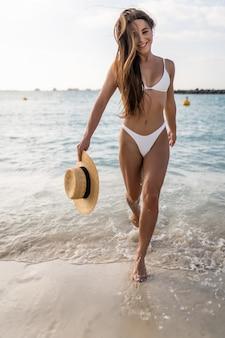 Junge frau im weißen bikini geht auf den strand