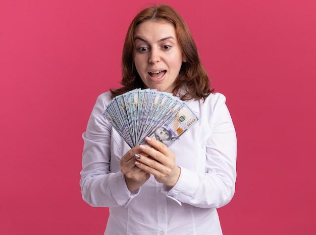 Junge frau im weißen hemd, das das geld betrachtet, das das glückliche und aufgeregte stehen des geldes über rosa wand betrachtet