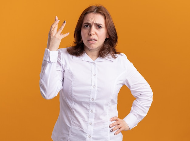 Junge frau im weißen hemd, das front betrachtet, missfällt, die hand im missfallen erhöht, das über orange wand steht