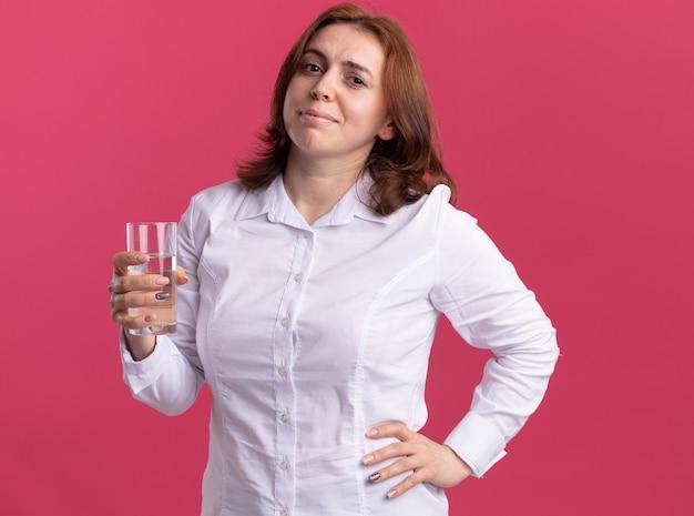 Junge frau im weißen hemd, das glas wasser hält, das vorne lächelnd steht und fröhlich über rosa wand steht