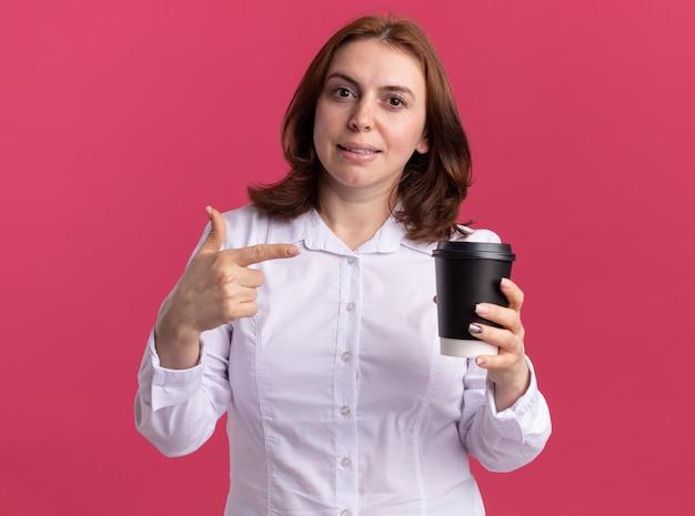 Junge frau im weißen hemd, das kaffeetasse hält, die mit zeigefinger darauf lächelt, zuversichtlich stehend über rosa wand