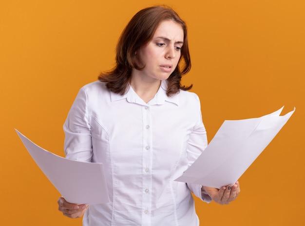 Junge frau im weißen hemd, das leere seiten hält, die sie verwirrt betrachten, die über orange wand stehen