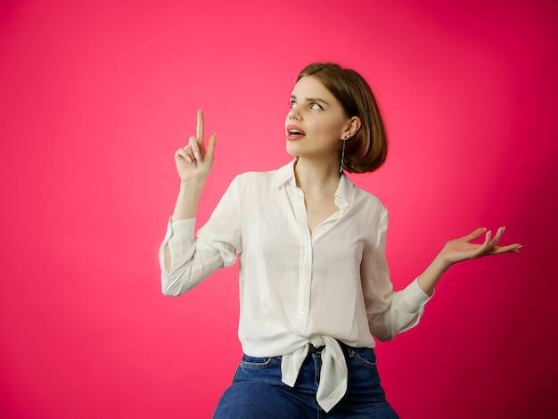 Junge frau im weißen hemd, das leeren kopienraum mit ihrem finger auf rosa zeigt