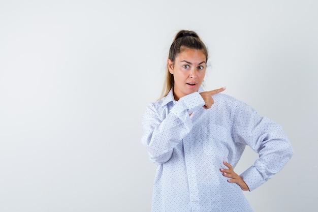 Junge frau im weißen hemd, das mit zeigefinger nach rechts zeigt, hand auf hüfte hält und überrascht schaut