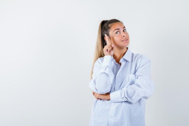 Junge frau im weißen hemd, das mit zeigefinger nach rechts zeigt und vernünftig aussieht