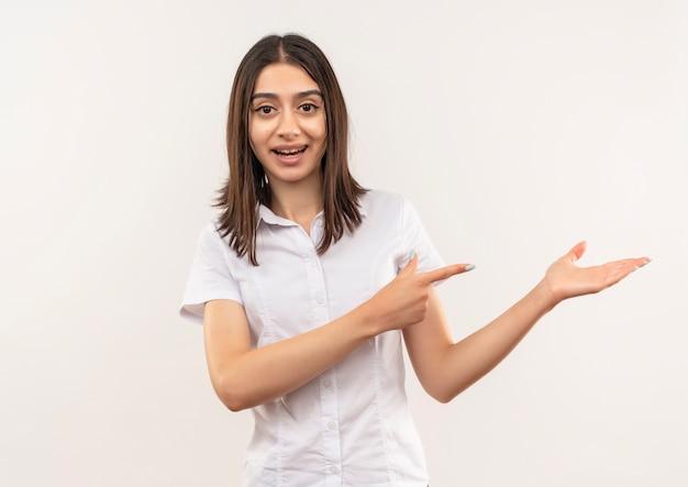 Junge frau im weißen hemd, das nach vorne lächelnd etwas präsentiert, das etwas mit arm ihrer hand zeigt, die mit finger zur seite zeigt, die über weißer wand steht