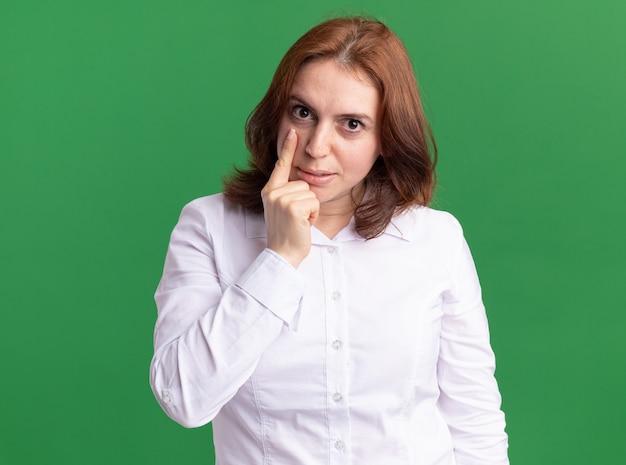 Junge frau im weißen hemd, das nach vorne zeigt, zeigt mit zeigefinger an ihrem auge, das über grüner wand steht