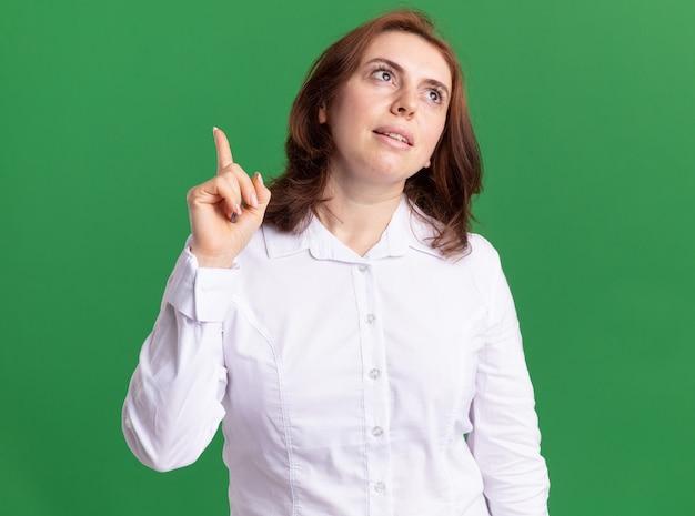 Junge frau im weißen hemd, das oben mit lächeln auf gesicht zeigt zeigefinger denkt, der über grüner wand steht