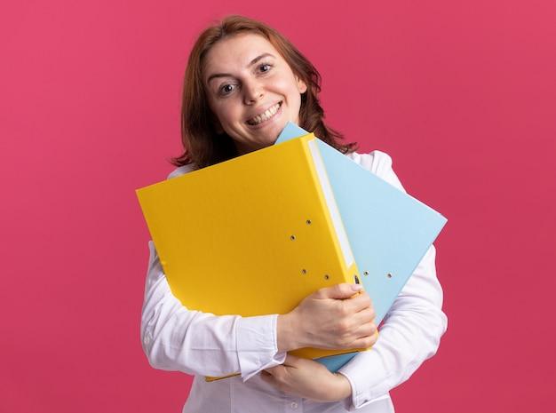 Junge frau im weißen hemd, das ordner betrachtet, die vorne lächelnd mit glücklichem gesicht stehen über rosa wand stehen