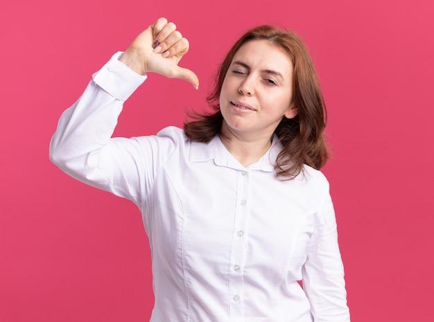 Junge frau im weißen hemd, das vorne lächelt und zwinkert und auf sich zeigt, wobei daumen über rosa wand steht