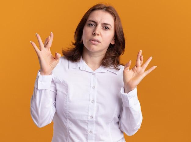Junge frau im weißen hemd, das vorne mit ernstem gesicht schaut, das finger über orange wand steht