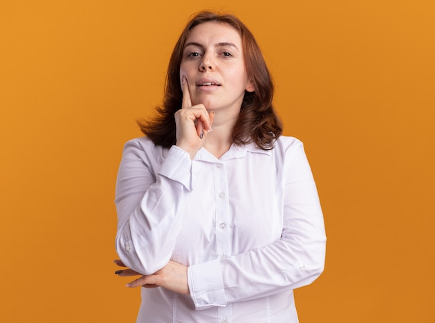 Junge frau im weißen hemd, das vorne mit nachdenklichem ausdruck betrachtet, der über orange wand steht