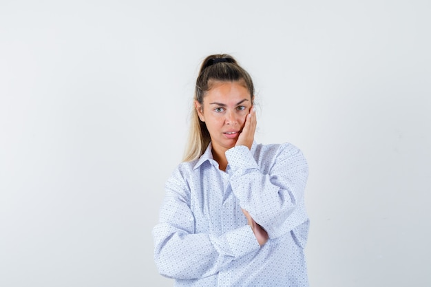 Junge frau im weißen hemd, das wange auf handfläche lehnt, während sie aufwirft und fröhlich schaut