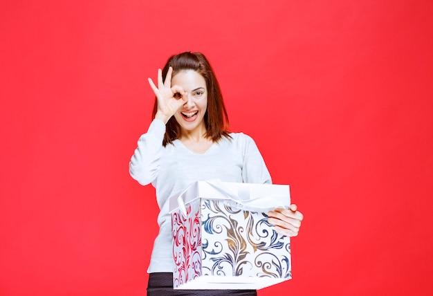 Junge frau im weißen hemd, die eine bedruckte geschenkbox hält und ein positives handzeichen zeigt