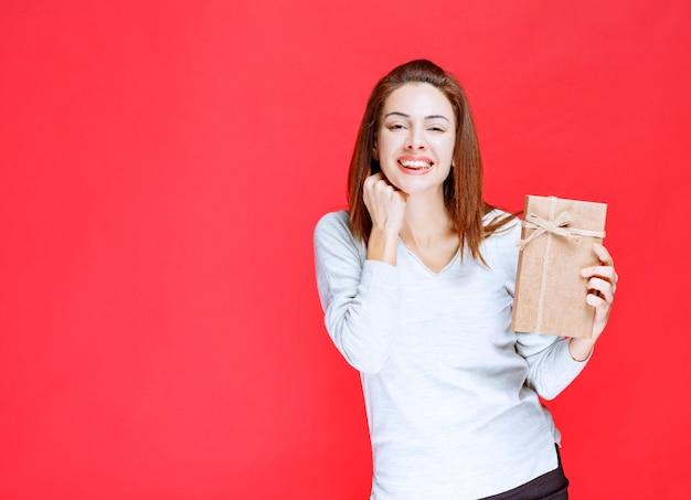 Junge frau im weißen hemd, die eine geschenkbox aus karton hält und überrascht aussieht