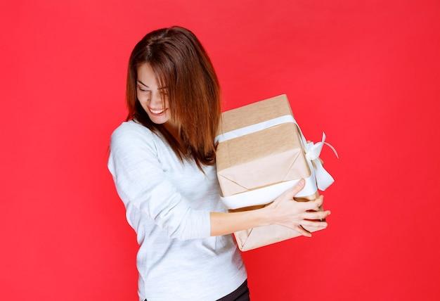 Junge frau im weißen hemd, die eine geschenkbox aus karton hält