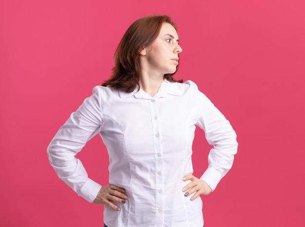 Junge frau im weißen hemd schaut beiseite mit ernstem gesicht mit armen an der hüfte, die über rosa wand steht