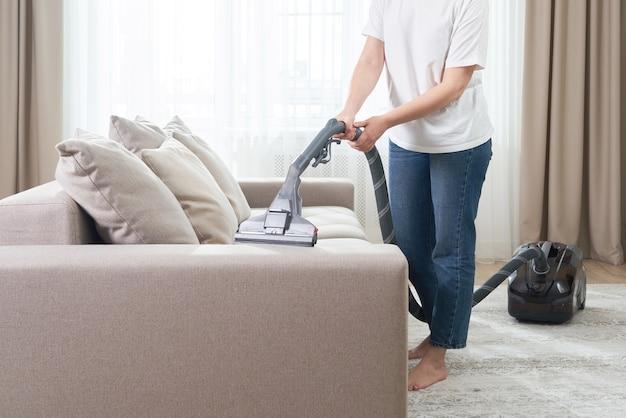 Junge frau im weißen hemd und im jeansreinigungsteppich unter sofa mit staubsauger im wohnzimmer, kopienraum. hausarbeit, reinigung und hausarbeit konzept