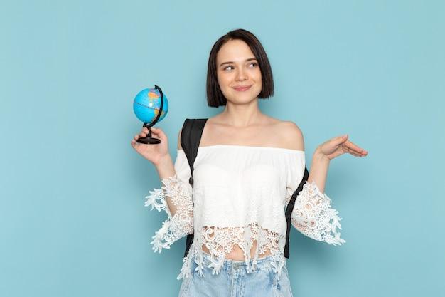 Junge frau im weißen hemd und in der schwarzen tasche, die kleinen globus auf blau hält