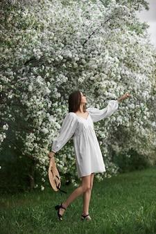Junge frau im weißen kleid mit strohhut geht durch den blühenden frühlingsgartenpark. der frühling ist gekommen, romantische stimmung