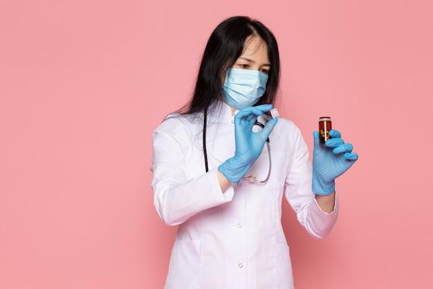 Junge frau im weißen medizinischen anzug blaue handschuhe blaue schutzmaske, die dose mit pillen auf rosa hält