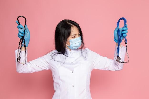 Junge frau im weißen medizinischen anzug blaue handschuhe blaue schutzmaske mit stethoskop auf rosa