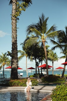 Junge frau im weißen peignoir und im bikini entspannen am außenpool unter exotischen palmen irgendwo im tropischen land. urlaub und sommerzeit.