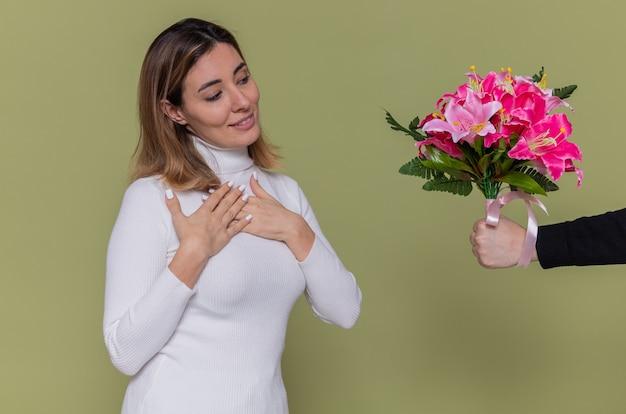 Junge frau im weißen rollkragenpullover, der händchenhalten auf ihrer brust lächelt und dankbare und positive gefühle empfängt, während sie blumenstrauß erhält