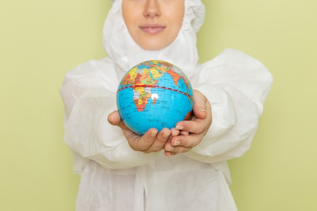 Junge frau im weißen spezialanzug und im gelben schutzhelm, der kleine runde kugel mit leichtem lächeln auf grün hält