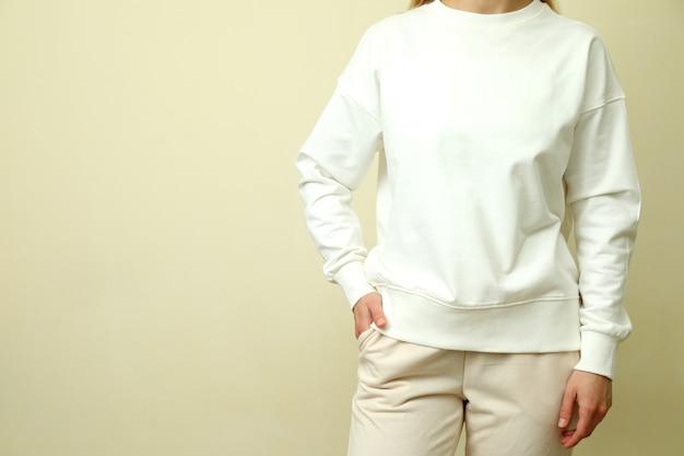 Junge frau im weißen sweatshirt gegen beigen hintergrund