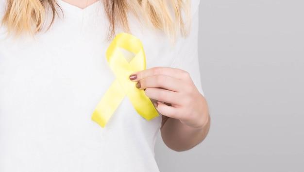 Junge frau im weißen t-shirt, das gelbes bandbewusstseinssymbol für selbstmord, sarkomknochenkrebs, blasenkrebs, leberkrebs und kinderkrebskonzept hält. gesundheitsvorsorge.