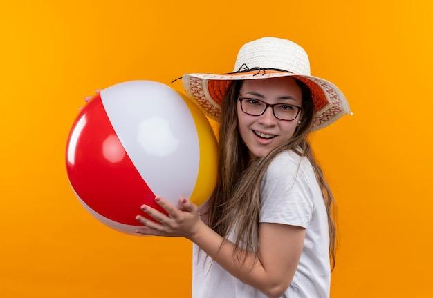 Junge frau im weißen t-shirt, das sommerhut hält, der aufblasbaren ball hält, der fröhlich über orange wand steht