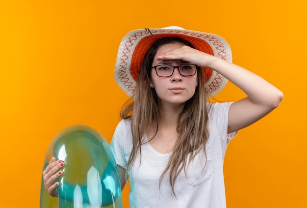 Junge frau im weißen t-shirt, das sommerhut hält, der aufblasbaren ring hält, der weit weg mit hand über kopf schaut, um jemanden oder etwas zu sehen, das über orange wand steht