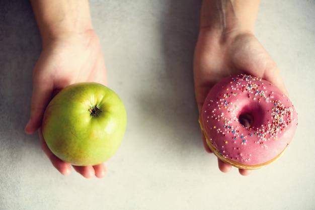 Junge frau im weißen t-shirt, das zwischen grünem apfel oder ungesunder fertigkost, donut wählt.