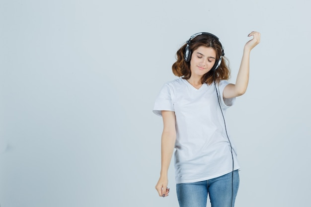Junge frau im weißen t-shirt, jeans, die musik mit kopfhörern genießen und munter, vorderansicht schauen.