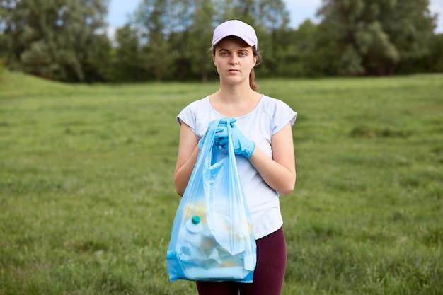 Junge frau im weißen t-shirt und in der baseballkappe, die blauen müllsack in den händen hält