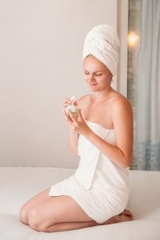 Junge frau im weißen tuch tragen feuchtigkeitscremecreme im schlafzimmer auf. hautpflege, spa-konzept