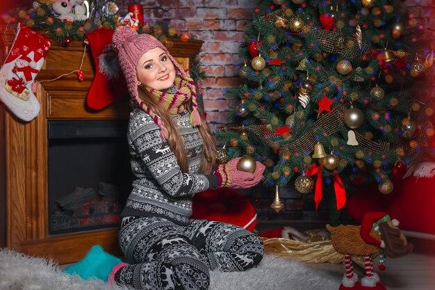 Junge frau im wollanzug mit hirsch schmückt weihnachtsbaum