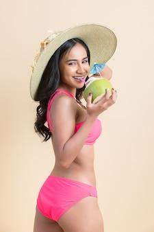 Junge frau in badebekleidung mit kokosnuss