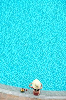 Junge frau in bikini und strohhut sitzt am rand des swimmingpools und genießt cocktails und frisches obst, blick von oben