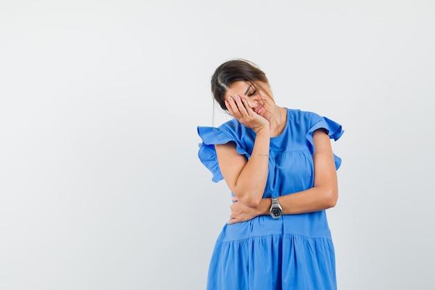 Junge frau in blauem kleid, das gesicht auf die handfläche lehnt und schläfrig aussieht
