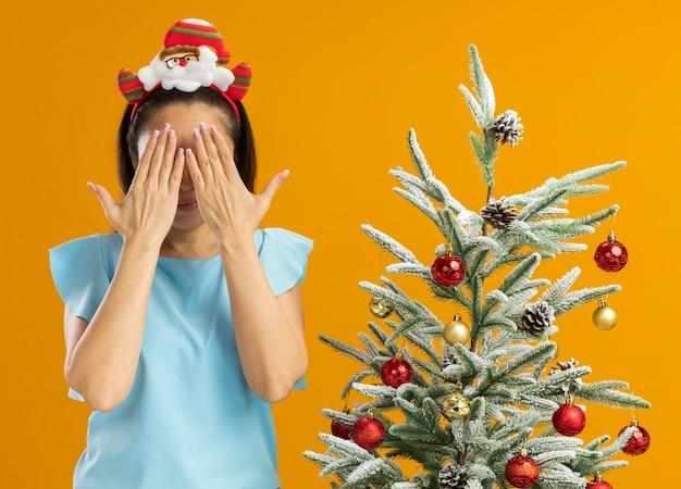 Junge frau in blauem oberteil mit lustigem weihnachtsrand auf kopfbedeckenden augen mit händen, die neben einem weihnachtsbaum über oranger wand stehen