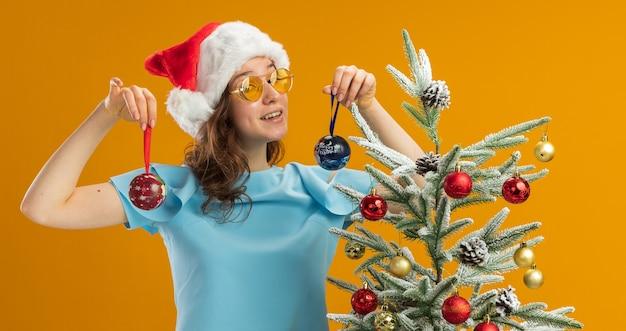 Junge frau in blauem oberteil und weihnachtsmütze mit gelber brille, die weihnachtskugeln hält und sie mit einem lächeln im gesicht betrachtet, das glücklich und positiv neben einem weihnachtsbaum über der orangefarbenen wand steht?